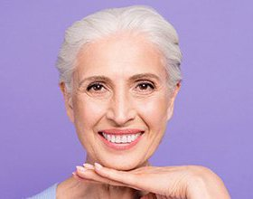 smiling older woman in front of a purple background