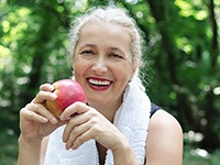 woman eating a red apple after exercising
