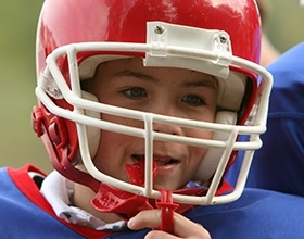 Young boy placing sports mouthguard