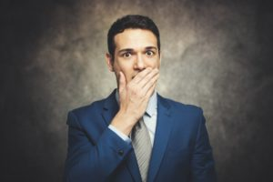 embarrassed man covering mouth