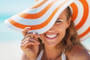 Smiling woman in sun hat and veneers in Boca Raton