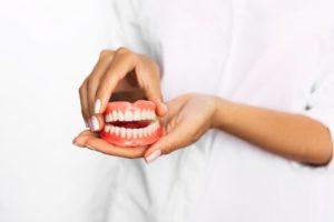 Closeup of dentist holding full set of dentures
